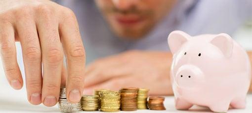 Mann stapelt Münzen neben seinem Sparschwein