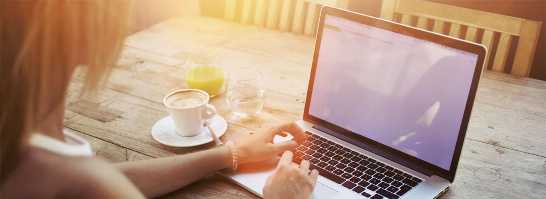 Psychologischer Berater Fernstudium - Frau sitzt bei Sonnenschein im freien am Laptop mit Orangensaft