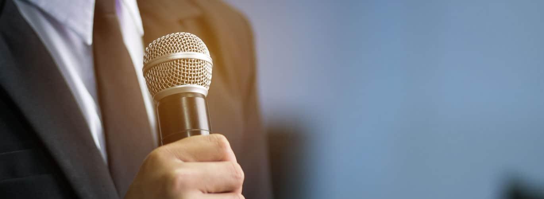 Kommunikationstrainer - Mann hält Mikrofon in der Hand
