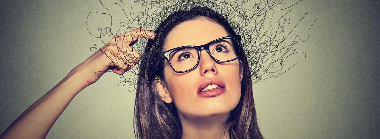 Stress-und-Mentalcoach - Frau fasst sich an den Kopf -  Gedanken strömen aus