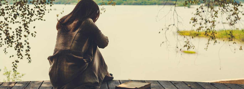 Psychologischer Berater - 5 Tipps um die EInsamkeit zu überwinden - Frau sitzt einsam am See