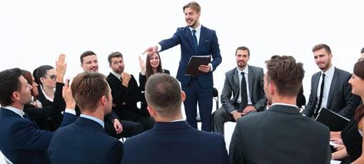 Verkäufer im Anzug steht zwischen gut gekleideten Menschen