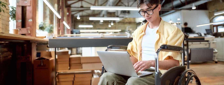 Fachkraft für Inklusion - Rollstuhlfahrer mit Laptop